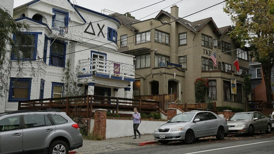 A woman walks down Channing Way past fraternities near the University of California, Berkeley campus Thursday, Oct. 27, 2016, in Berkeley, Calif. UC Berkeley's fraternity and sorority parties are back on this weekend, after a weeklong self-imposed ban. But there will be new guidelines that members say are aimed at eliminating sexual assaults.(AP Photo/Eric Risberg)