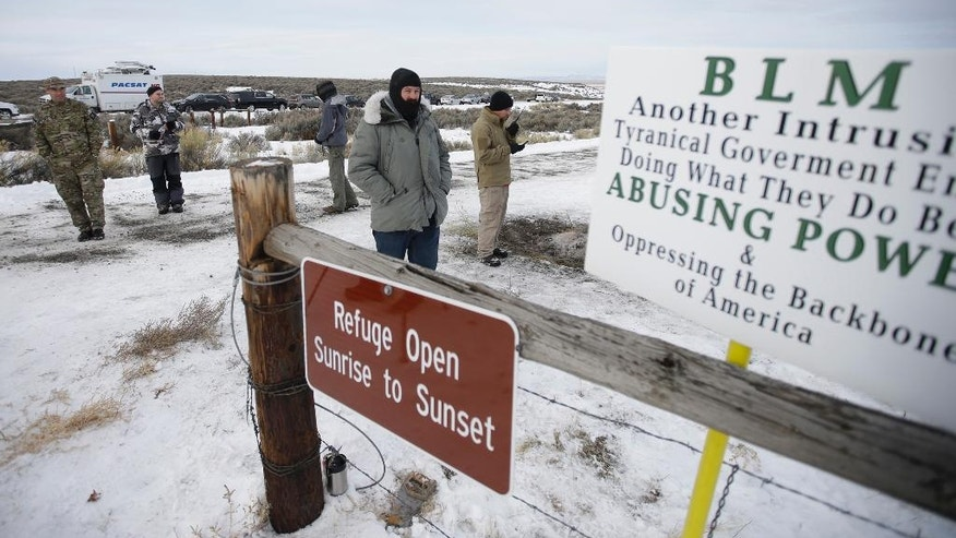 FILE - In this Monday, Jan. 4, 2016, file photo, members of the group occupying the Malheur National Wildlife Refuge headquarters stand guard near Burns, Ore. The leaders of an armed group that took over a national wildlife refuge in rural Oregon have been found not guilty of conspiracy and possession of firearms at a federal facility. A jury on Thursday, Oct. 27, 2016, exonerated brothers Ammon and Ryan Bundy and five others of conspiring to impede federal workers from their jobs at the Malheur National Wildlife Refuge. (AP Photo/Rick Bowmer, File)