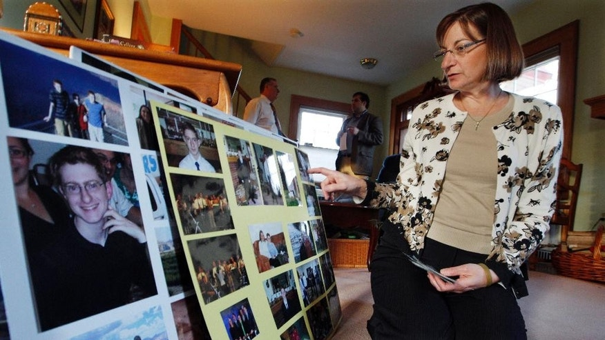 FILE – In this Dec. 9, 2011, file photo, Jane Clementi, right, the mother of Tyler Clementi, looks at family photographs as her husband Joseph Clementi, back left, the father of Tyler Clementi, speaks to a reporter in their home in Ridgewood, N.J. Former Rutgers University student Dharun Ravi, whose roommate Tyler Clementi killed himself in 2010 after being captured on a webcam kissing another man, pleaded guilty Thursday, Oct. 27, 2016, to attempted invasion of privacy, and was sentenced to probation and 30 days time served. (AP Photo/Mel Evans, File)