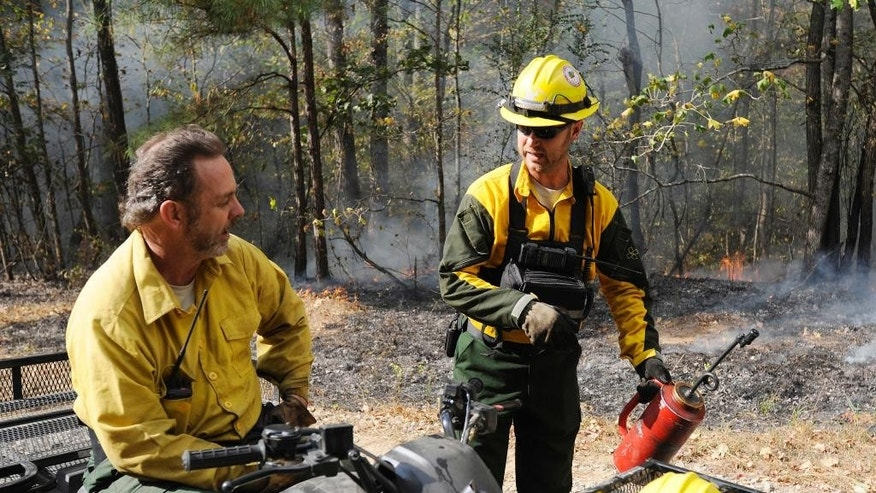 Alabama Forestry Commission firefighters Jim Junkin, left, and Brad Lang talk about strategies for fighting a wildfire near Brookside, Ala., on Thursday, Oct. 27, 2016.