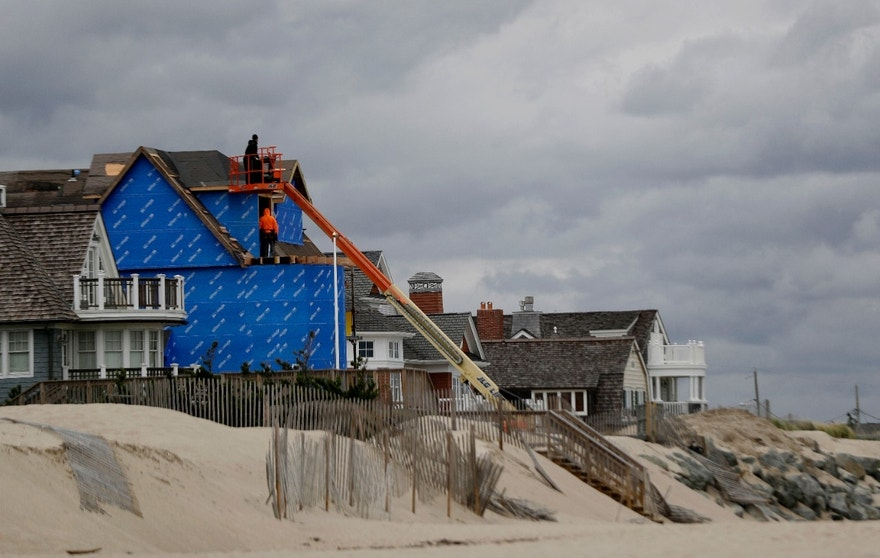 In a photo taken Thursday, Oct. 27, 2016, construction workers labor on a beachfront home in Bay Head, N.J. Sandy damaged or destroyed virtually every one of the 521 homes in neighboring Mantoloking, N.J., including dozens that were swept clean off the map, some coming to rest in a bay or even atop a drawbridge.  People have worked hard, and mostly successfully, over the past four years to restore the New York and New Jersey coastline to what it was before Superstorm Sandy crashed ashore. But some areas have not recovered, nor will they ever from the Oct. 29, 2012, storm.  (AP Photo/Julio Cortez)