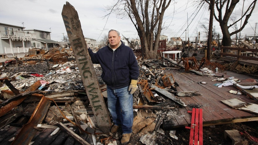 FILE - In this Nov. 15, 2012 file photo, Dean Rasinya poses with a street sign for Irving Walk salvaged from wreckage in the Breezy Point section of the Queens borough of New York. A fire destroyed more than 100 homes in the oceanfront community during Superstorm Sandy. Rasinya's home was flooded and suffered some fire damage but he is repairing the damage. (AP Photo/Mark Lennihan, File)