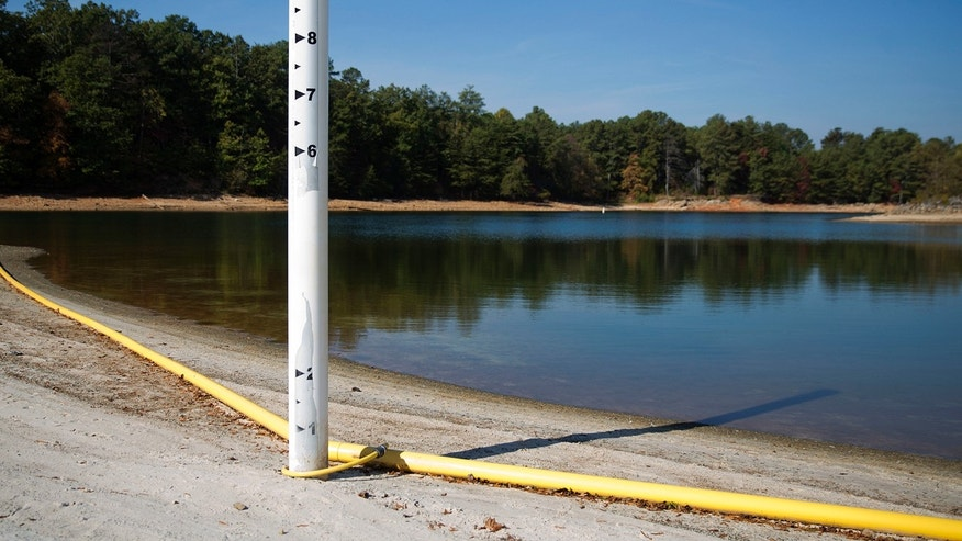 In this Wednesday, Oct. 26, 2016 photo, a floating swim line lays on the shore as Lake Lanier water levels stand about eight feet below normal in Buford, Ga.