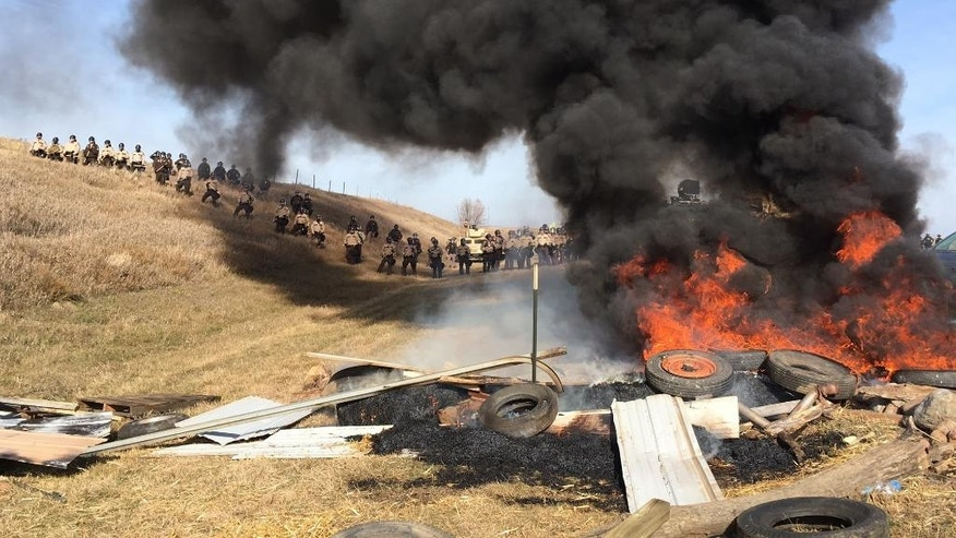 Tires burn as armed soldiers and law enforcement officers stand in formation on Thursday, Oct. 27, 2016, to force Dakota Access pipeline protesters off private land where they had camped to block construction. The pipeline is to carry oil from western North Dakota through South Dakota and Iowa to an existing pipeline in Patoka, Ill. (Mike McCleary/The Bismarck Tribune via AP)