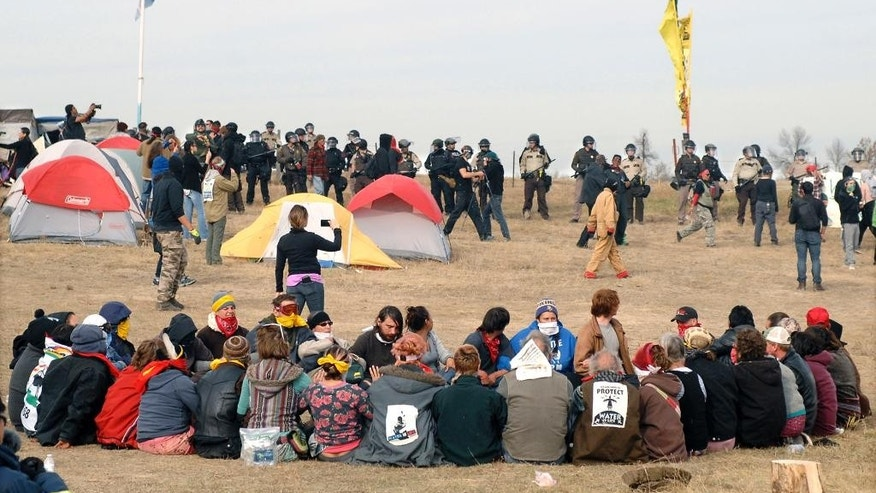FILE - In this Oct. 27, 2016 file photo, Dakota Access Pipeline protesters sit in a prayer circle at the Front Line Camp as a line of law enforcement officers make their way across the camp to remove the protesters and relocate to the overflow camp a few miles to the south on Highway 1806 in Morton County, N.D. Members of more than 200 tribes from across North America have come to the Standing Rock Sioux Tribe's encampment at the confluence of the Missouri and Cannonball rivers since August, the tribe says. Estimates at the protest site have varied from a few hundred to several thousand depending on the day _ enough for tribal officials to call it one of the largest gatherings of Native Americans in a century or more. (Mike McCleary/The Bismarck Tribune via AP, File)