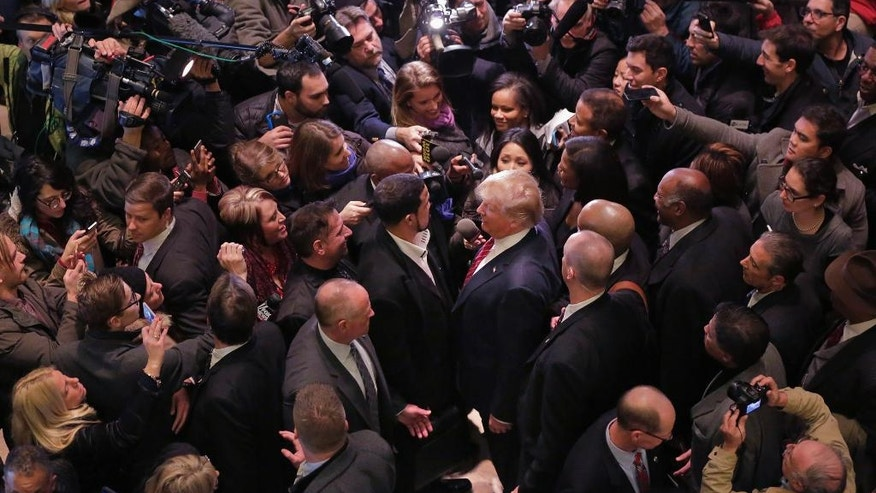 FILE - In this Monday, Nov. 30, 2015 file photo, Republican presidential candidate Donald Trump, center right, says goodbye to Dr. Darrell Scott, foreground left center, the senior pastor of New Spirit Revival Ministries in Cleveland Heights, Ohio, surrounded by media in the lobby of Trump Tower in New York, after meeting a coalition of 100 African-American evangelical pastors and religious leaders. (AP Photo/Richard Drew)