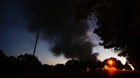 Light from a light pole shows a house near a plume of smoke from a Colonial Pipeline explosion, Monday, Oct. 31, 2016, in Helena, Ala. Colonial Pipeline said in a statement that it has shut down its main pipeline in Alabama after the explosion in a rural part of the state outside Birmingham. (AP Photo/Brynn Anderson)