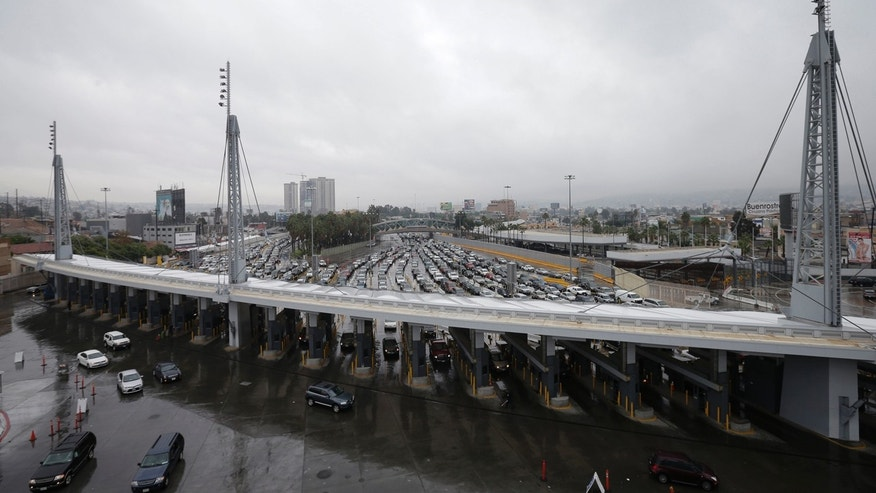 FILE - In this Dec. 3, 2014, file photo, cars wait to enter the United States from Tijuana, Mexico, through the San Ysidro port of entry in San Diego.