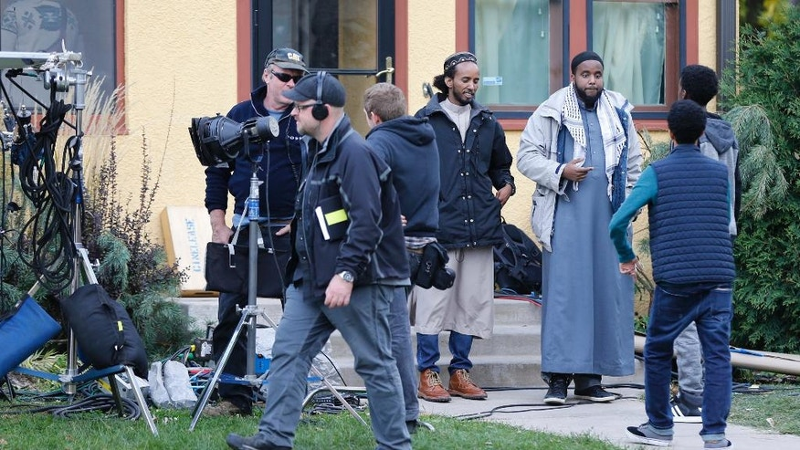 "In this Oct. 12, 2016 photo, Somali actors and film crew wait outside a home in Minneapolis for their role in filming of the proposed HBO series ""Mogadishu, Minnesota."" Somali-Canadian rapper, K'naan, who is directing and writing the proposed series, wants to tell a story of an immigrant coming to America and trying to adjust. (AP Photo/Jim Mone)"