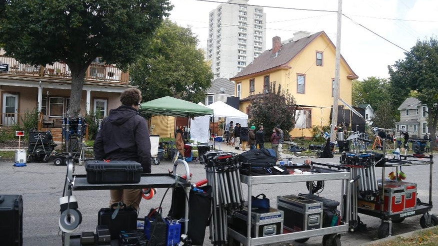"""In this Oct. 12, 2016 photo, a movie crew gathers outside a home in Minneapolis for filming of the proposed HBO series """"Mogadishu, Minnesota."""" Somali-Canadian rapper, K'naan, who is directing and writing the proposed series, wants to tell a story of an immigrant coming to America and trying to adjust. (AP Photo/Jim Mone)"""