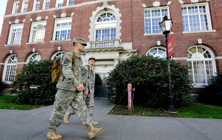 In this Thursday, Oct. 13, 2016 photo Brown University students and U.S. Army ROTC cadets William Summers, of Wailuku, Hawaii, left, and Cat Carignan, of Boise, Idaho, right, walk together on the schools campus, in Providence, R.I. Ivy League schools seek to step up recruitment of veterans, who are hugely underrepresented when compared with state schools. (AP Photo/Steven Senne)