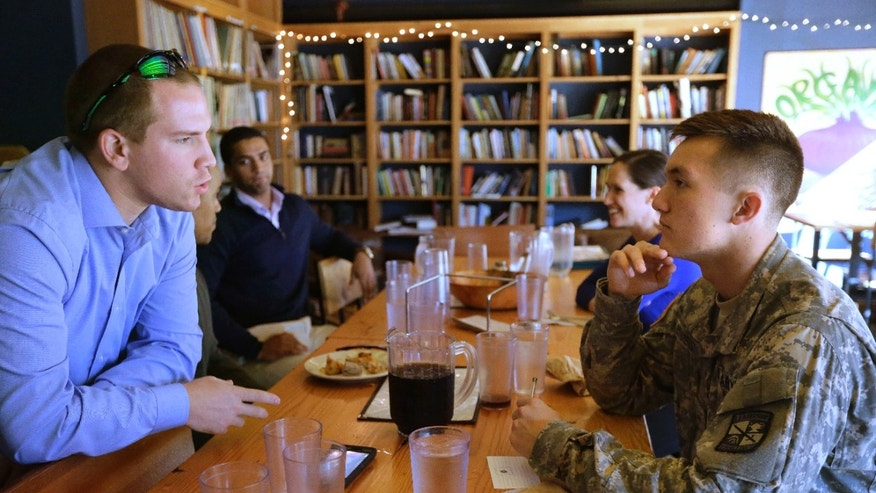 In this Thursday, Oct. 13, 2016 photo U.S. Army reservist and Brown University student Evan Stern, of Oradell, N.J., left, speaks with Brown University student and ROTC cadet William Summers, of Wailuku, Hawaii, right, during a luncheon at a pizza restaurant near the school's campus, in Providence, R.I.