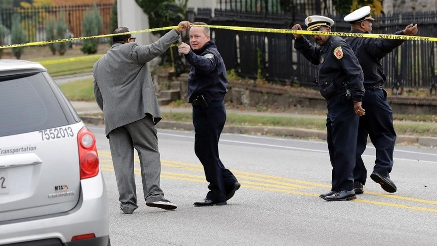 Baltimore Police Department commissioner Kevin Davis, second from left, approaches the scene of an early morning fatal collision between a school bus and a commuter bus in Baltimore, Tuesday, Nov. 1, 2016.  Baltimore police spokesman T.J. Smith said the school bus rear ended a car Tuesday morning, then struck a pillar at a cemetery and veered into oncoming traffic, hitting the Maryland Transit Administration bus on the driver's side.  (AP Photo/Patrick Semansky)