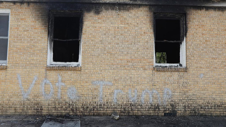 """Vote Trump"" is spray painted on the side of the fire damaged Hopewell M.B. Baptist Church in Greenville, Miss., Wednesday, Nov. 2, 2016.  Fire Chief Ruben Brown tells The Associated Press that firefighters found flames and smoke pouring from the sanctuary of the church just after 9 p.m. Tuesday. (AP Photo/Rogelio V. Solis)"