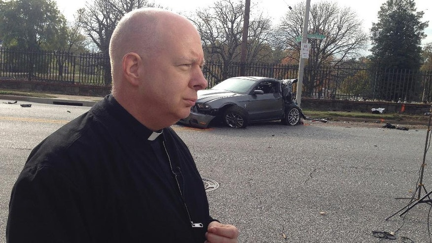 """The Rev. Mike Murphy who heard the crash from his room in the rectory of nearby St. Joseph's Monastery speaks to a reporter, Tuesday, Nov. 1, 2016, in Baltimore. """"It was fast,"""" he said. """"It was like one loud thump. A school bus blocks away from its first stop Tuesday morning rear-ended a car, hit the entrance to a cemetery and then veered into an oncoming commuter bus in a crash that killed at least six people and injured 10, authorities said. (AP Photo/Brian Witte)"""