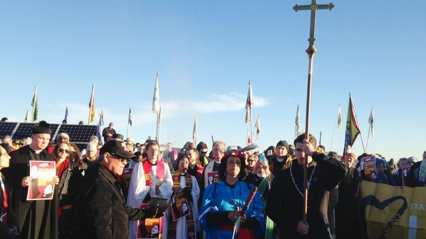 Members of the clergy join protesters against the Dakota Access oil pipeline in southern North Dakota near Cannon Ball on Thursday, Nov. 3, 2016, to draw attention to the concerns of the Standing Rock Sioux and push elected officials to call for a halt to construction. The tribe says the $3.8 billion, four-state pipeline threatens its drinking water and cultural sites. (AP Photo/James MacPherson)