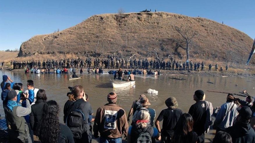 Dakota Access Pipeline protesters stand in the foreground and in the waist-deep water of the Cantapeta Creek, northeast of the Oceti Sakowin Camp, near Cannon Ball, N.D., Wednesday, Nov. 2, 2016. Officers in riot gear clashed again Wednesday with protesters near the Dakota Access pipeline, hitting dozens with pepper spray as they waded through waist-deep water in an attempt to reach property owned by the pipeline's developer. (Mike Mccleary/The Bismarck Tribune via AP)