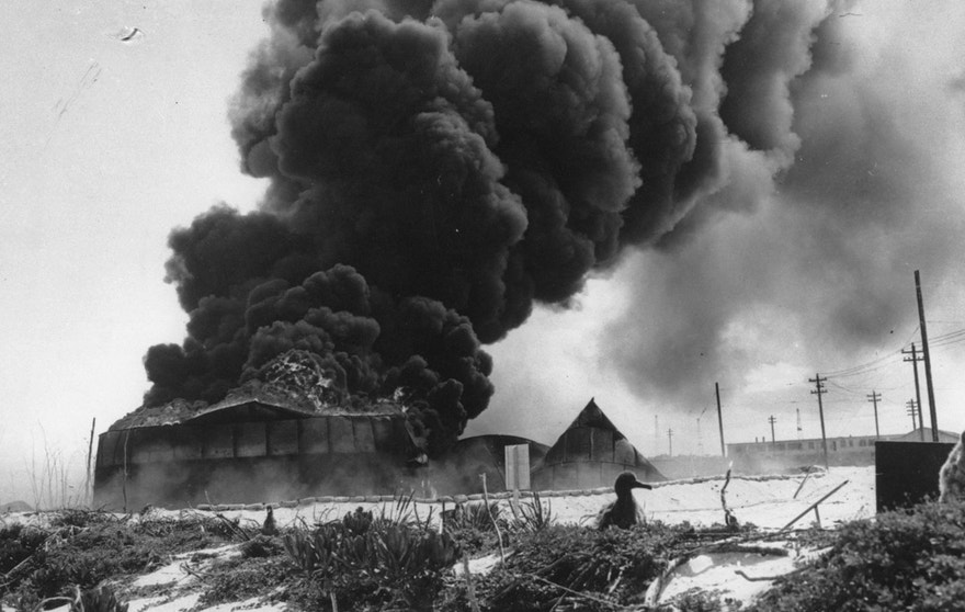 FILE — In this June, 1942 file photo, black smoke rises from a burning U.S. oil tank, set afire during the Battle of Midway on Midway Atoll in the Northwestern Hawaiian Islands. The Battle of Midway was a major turning point in World War II's Pacific theater. The remote atoll where thousands died is now a delicate sanctuary for millions of seabirds, and a new battle is pitting preservation of its vaunted military history against the protection of its wildlife.  (AP Photo)