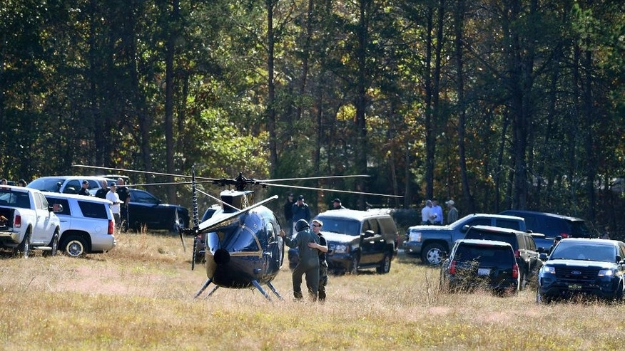 The Greenville County Sheriff's Office assists Spartanburg County investigators Friday, Nov. 4, 2016, as they work on the Wofford Road property in Woodruff, S.C., where a missing woman was found Thursday chained in a large storage container. (Heidi Heilbrunn /The Greenville News via AP)