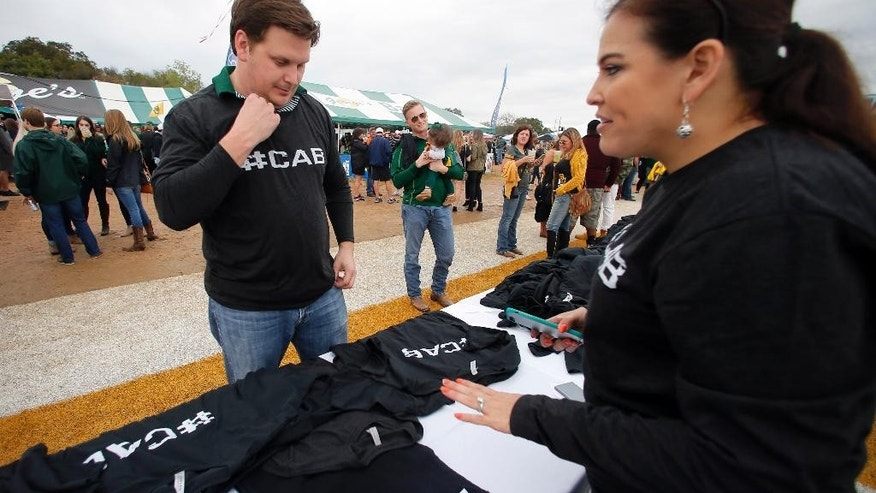 Baylor fan Jon McClellan of Houston, purchases several shirts from Celsa Hurley of Hurley's Graphics which have the word #CAB on printed on them, before an NCAA college football game against TCU on Saturday, Nov. 5, 2016, in Waco, Texas. The #CAB stands for Coach Art Briles, Baylor's former football head coach. (AP Photo/Tony Gutierrez)