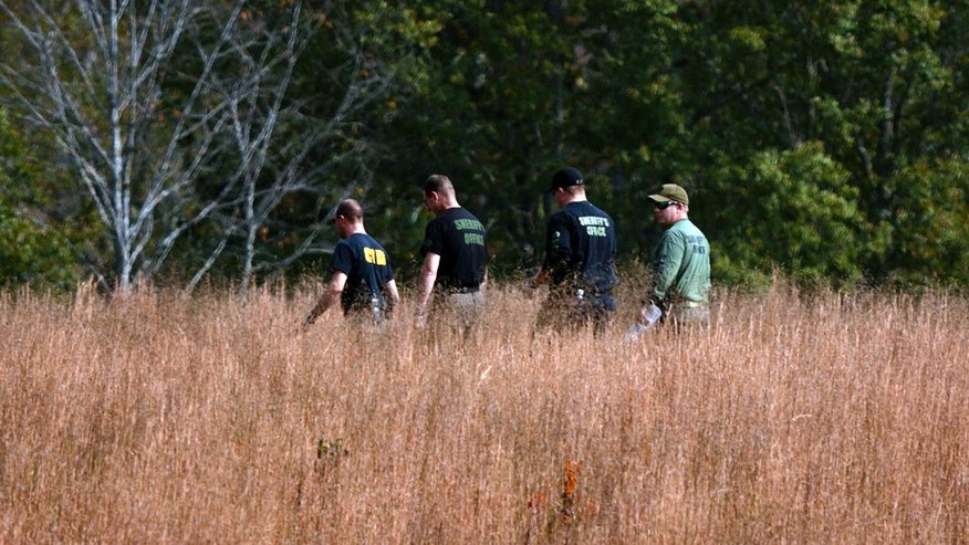 In this Thursday, Nov. 3, 2016 photo, police search a field on property owned by Todd Kohlhepp where a missing woman was found chained up in a large storage container in Woodruff, S.C.   (Tim Kimzey/The Spartanburg Herald-Journal via AP)