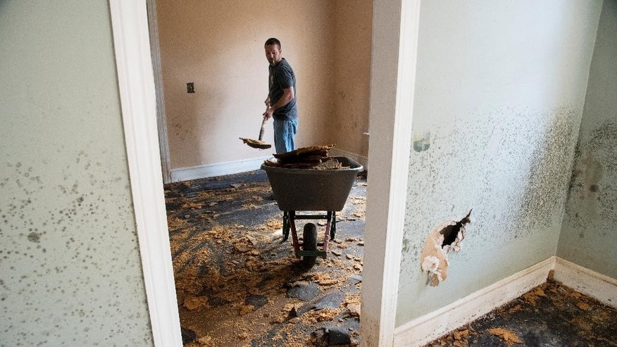 Brent Davis helps clean out a home that was heavily damaged by floodwaters caused by rain from Hurricane Matthew in Nichols, S.C., Thursday, Oct. 27, 2016.  Nearly a month since floodwaters consumed the town, few have returned. The fear is that many never will. A stew of contaminants stood inches to feet deep in homes for a week. As it receded, toxic black mold grew rampant, leaving nearly all of the town's 261 homes uninhabitable. Few, if any, had flood insurance. (AP Photo/Mike Spencer)