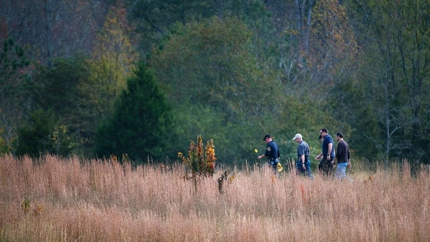 In this Thursday, Nov. 3, 2016 photo, police search a field on property owned by Todd Kohlhepp where a missing woman was found chained up in a large storage container in Woodruff, S.C.  (Lauren Petracca/The Greenville News via AP)