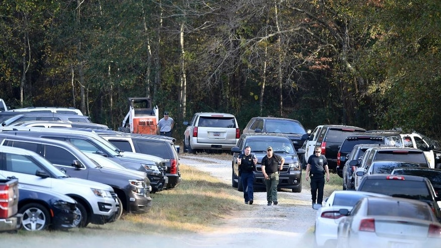In this Thursday, Nov. 3, 2016, investigators gather at property on Wofford Road in Woodruff, S.C., after a missing Anderson woman was found chained in a large storage container. (Heidi Heilbrunn/The Greenville News via AP)