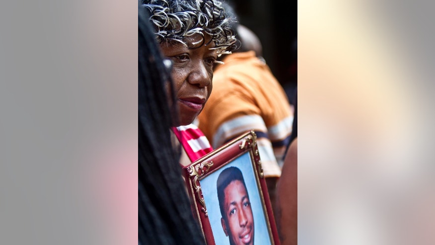 FILE - In this July 7, 2015, file photo, Gwen Carr holds a picture of her son Eric Garner during a news conference in New York with relatives of New Yorkers killed by police. died in July 2014 in New York City after a white officer placed him in a chokehold during an arrest for selling loose cigarettes. A grand jury declined to indict the officer who put Garner in the hold or any of the other officers involved in the arrest. The city agreed to pay a $6 million civil settlement. (AP Photo/Bebeto Matthews, File)
