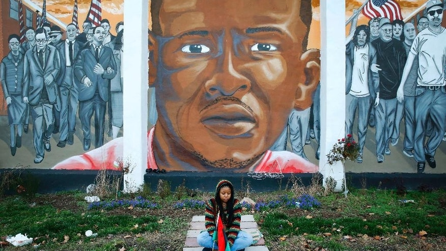 FILE - In a Dec. 16, 2015 file photo, Jazmin Holloway sits below a mural depicting Freddie Gray at the intersection of his arrest, in Baltimore. The first effort to find a police officer criminally responsible for Freddie Gray's death from a broken neck in a police van ended Wednesday with a hung jury and a mistrial. Gray's death led to rioting. Prosecutors in July 2016 said they were dropping charges against the remaining police officers awaiting trial, leaving no convictions against six officers who were charged initially in the case. Gray's family agreed to a $6.4 million settlement with the city in September 2015.(AP Photo/Patrick Semansky, File)