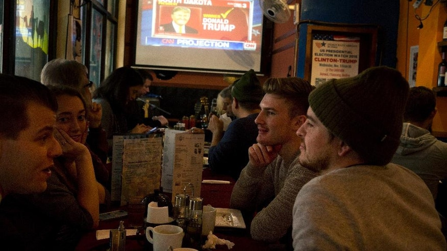 Patrons gather at a restaurant to watch the live telecast of the U.S. presidential elections on TV in Beijing, China, Wednesday, Nov. 9, 2016.  The United States headed for the polls to vote for their new president on Tuesday.  (AP Photo/Ng Han Guan)