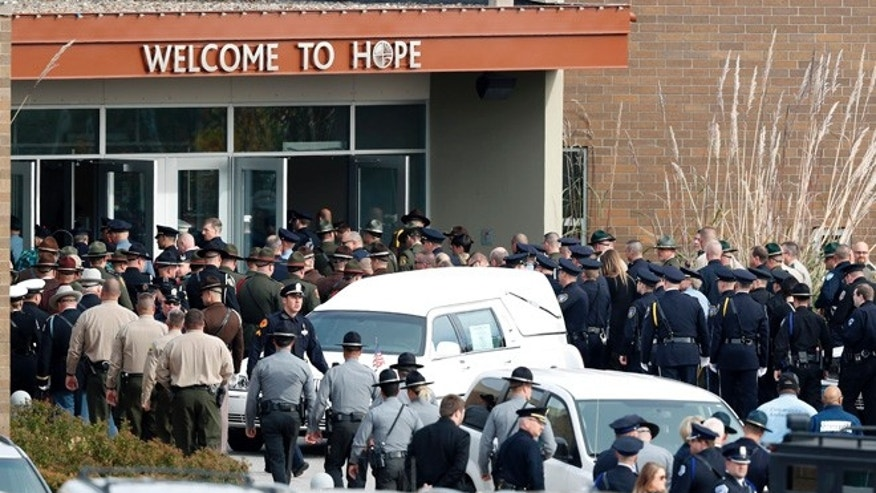 Law enforcement officers enter the Lutheran Church of Hope before funeral services for Des Moines police officer Sgt. Anthony Beminio