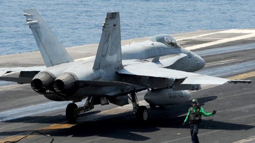 An F/A-18C Hornet assigned to the Valions of Strike Fighter Squadron (VFA) 15 moves across the flight deck of the aircraft carrier USS George H.W. Bush (CVN 77).