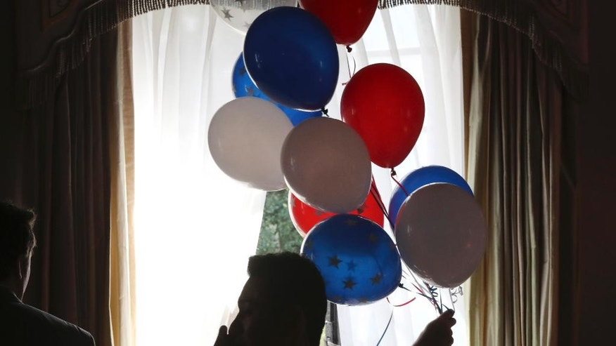 A staff carries balloons to decorate the venue during a live broadcasting of the 2016 U.S. Presidential Election results at U.S. Ambassador's residence in Tokyo, Wednesday, Nov. 9, 2016. (AP Photo/Eugene Hoshiko)