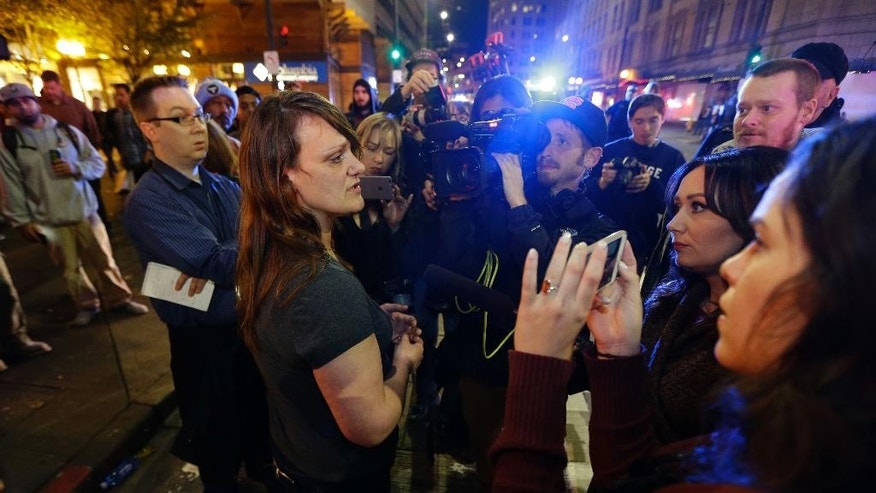 Sharon Keith, center-left, who works in a store near where a shooting took place, Wednesday, Nov. 9, 2016, in downtown Seattle, cries as she talks to reporters about the shooting. Authorities say a man escaped on foot after firing into a crowd and wounding five people outside a convenience store in downtown Seattle. (AP Photo/Ted S. Warren)