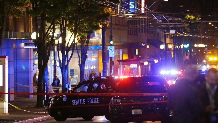 Police cars are staged at the scene of a shooting Wednesday, Nov. 9, 2016, in downtown Seattle. Authorities say a man escaped on foot after firing into a crowd and wounding five people outside a convenience store in downtown Seattle.   (AP Photo/Ted S. Warren)