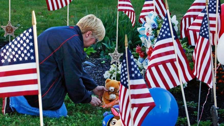 Becky Travaglini, of Canonsburg, Pa., places a teddy bear at a makeshift memorial for the Canonsburg police officers who were shot when they responded to a domestic call early Thursday, Nov 10, 2016, in Canonsburg, Pa. (AP Photo/Gene J. Puskar)