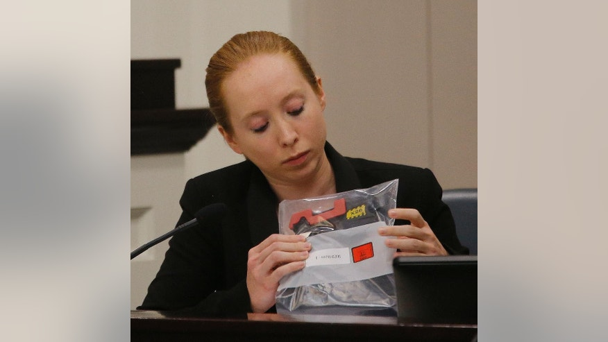 Witness, crime scene investigator, Jamie Johnson looks over former North Charleston Police Officer Michael Slager's taser x26 during the murder Slager's murder trial , Wednesday, Nov. 9, 2016, in Charleston, S.C. Slager is on trial facing a murder charge in the shooting death of Walter Scott, who was gunned down after he fled from a traffic stop. (Grace Beahm/Post and Courier via AP, Pool)
