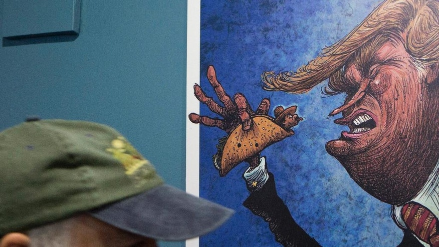 "An American visitor walks past a cartoon of a Mexican wrapped in a taco sticking his tongue out at a depiction of President-elect Donald Trump, in an exhibition titled; ""Trump: A wall of caricatures,"" at the Caricature Museum in downtown Mexico City, Thursday, Nov. 10, 2016. The exhibition, which features dozens of works by Mexican and international cartoonists, mocks amongst other things Trump's derogatory statements about Mexicans and his plans to build a wall between the two countries.(AP Photo/Rebecca Blackwell)"