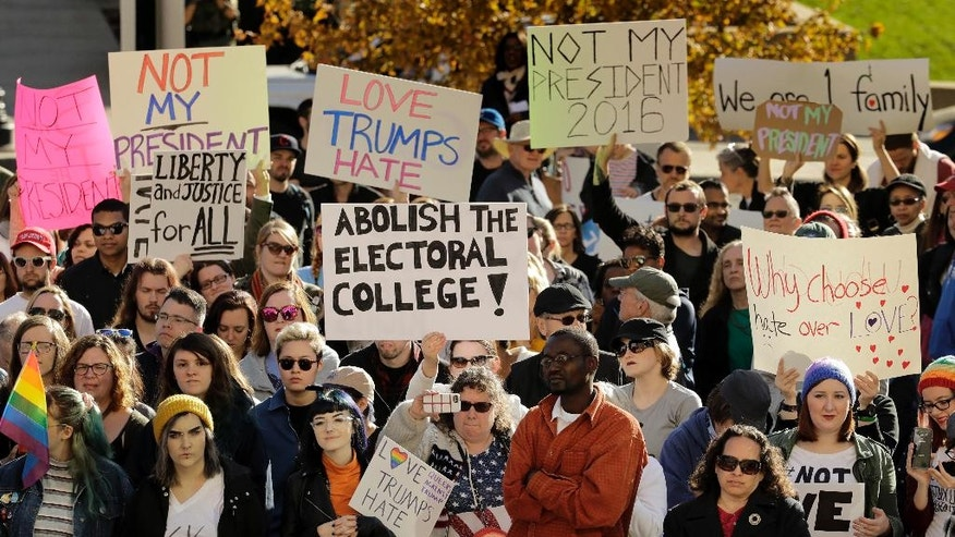 People protest against the election of President-elect Donald Trump Saturday, Nov. 12, 2016, in front of City Hall in Kansas City, Mo. Thousands took to the streets Saturday across the United States as demonstrations against Trump continued in New York, Chicago, Los Angeles and beyond. (AP Photo/Charlie Riedel)