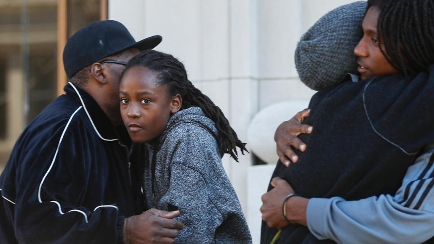 Family and friends of Sam DuBose embrace outside the Hamilton County Courthouse after a mistrial is declared due to a hung jury in the murder trial against Ray Tensing, Saturday, Nov. 12, 2016, in Cincinnati. Tensing, a white former University of Cincinnati police officer, was charged with murder in the shooting of DuBose, an unarmed black motorist, while on duty during a routine traffic stop on July 19, 2015. (AP Photo/John Minchillo)