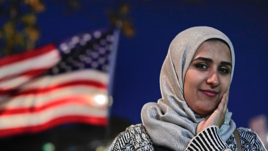 "Enas Almadhwahi, an immigration outreach organizer for the Arab American Association of New York, stands for a photo along Fifth Avenue in the Bay Ridge neighborhood of Brooklyn, Friday, Nov. 11, 2016, in New York. After the election of Donald Trump as president of the United States, she says, ""Everything feels like it's upside down. ... I still like to hope Trump will change his words about Muslims."" (AP Photo/Julie Jacobson)"