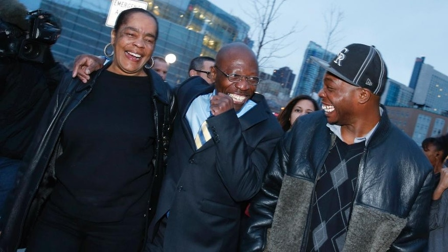"FILE - In this Dec. 22, 2015, file photo, Clarence Moses-EL, center, flanked by his wife Stephanie Burke, left,  and an unidentified man jokes after his release from the Denver County jail in Denver. Moses-EL, released from prison last year after spending more than a quarter of a century in prison for a rape he long denied committing, was acquitted of the crime on Monday, Nov. 14, 2016, leaving a courtroom to applause from supporters and chants of ""it's over."" (AP Photo/David Zalubowski, File)"