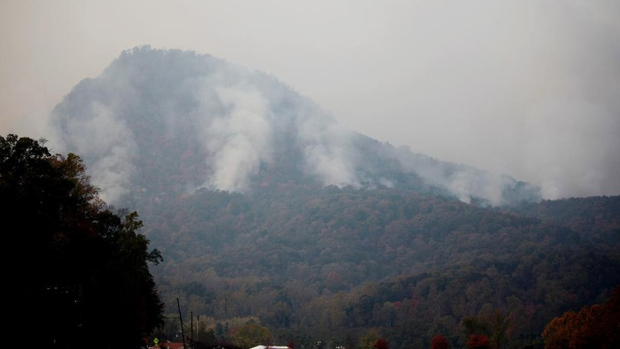 In a Saturday, Nov. 12, 2016 photo, smoke billows from the Party Rock fire in Lake Lure, NC. North Carolina Gov. Pat McCrory on Monday, Nov. 14, planned to update residents on wildfires in western North Carolina as officials report some progress in containing the blazes. (Angela Wilhelm/The Asheville Citizen-Times via AP)