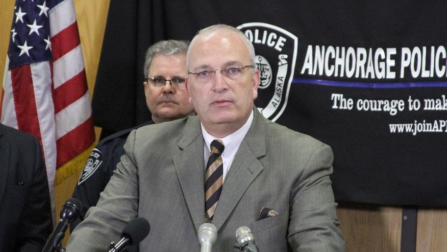 Anchorage Police Lt. John McKinnon speaks at a news conference in Anchorage, Alaska, on Tuesday, Nov. 15, 2016. McKinnon said the gun used in the shooting of an officer over the weekend, was linked through ballistics to the same gun used in five unsolved homicides this year. Behind McKinnon is Anchorage Police Chief Chris Tolley.  (AP Photo/Mark Thiessen)