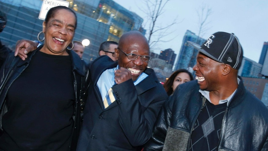 FILE - In this Dec. 22, 2015, file photo, Clarence Moses-EL, center, flanked by his wife Stephanie Burke, left, and an unidentified man jokes after his release from the Denver County jail in Denver