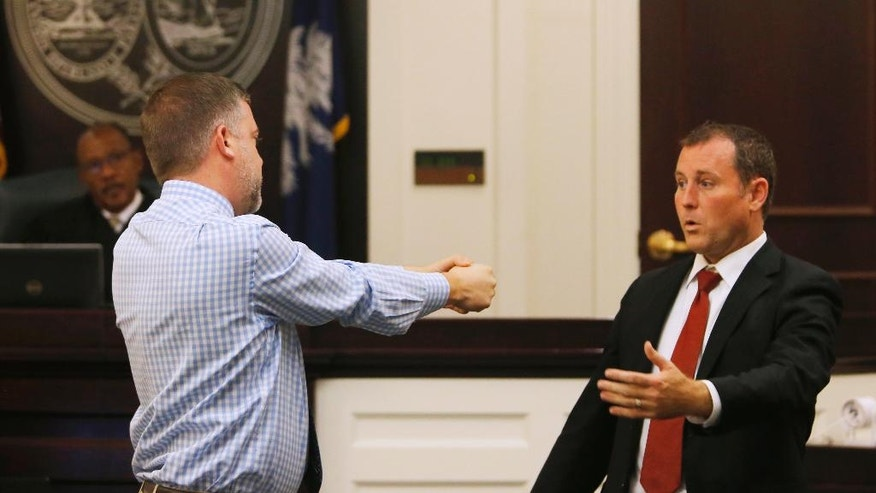 Levi Miles, left, a private investigator, gestures towards Assistant Solicitor Chad Simpson, to demonstrate how Michael Slager said Walter Scott came at him with a taser, in the trial of former North Charleston Police officer Michael Slager at Charleston County court in Charleston, SC., Monday, Nov. 14, 2016. (Grace Beahm/Post and Courier via AP, Pool)