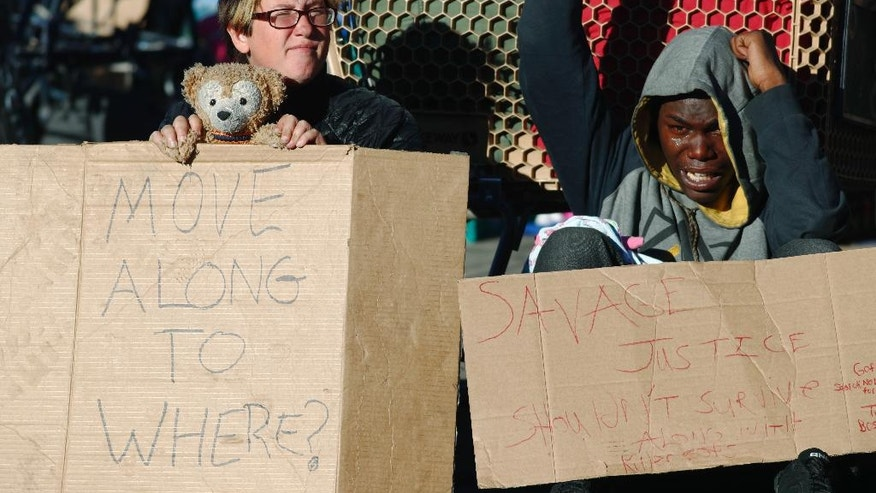 Shannon Wolf, left, and a man who identified himself as King Reality hold homemade placards to protest during a sweep of homeless people who were living on the walks surrounding a shelter near the baseball stadium Tuesday, Nov. 15, 2016, in downtown Denver. A new report from The National Law Center on Homelessness and Poverty said Tuesday, Nov. 15, 2016, that cities nationwide such as Denver are enacting more policies that criminalize homelessness. (AP Photo/David Zalubowski)