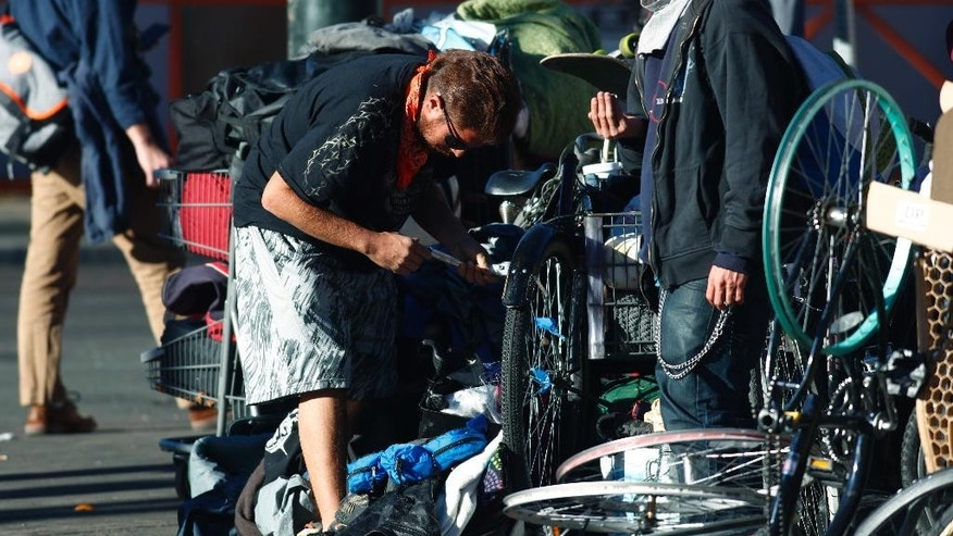 Unidentified men pack up their belongings during a sweep of homeless people who were living on the walks surrounding a shelter near the baseball stadium Tuesday, Nov. 15, 2016, in downtown Denver.  new report from The National Law Center on Homelessness and Poverty said Tuesday, Nov. 15, 2016, that cities nationwide such as Denver are enacting more policies that criminalize homelessness. (AP Photo/David Zalubowski)