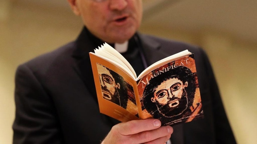 The face of Jesus Christ is seen on a booklet as Auxiliary Bishop Joseph Brennan, of Los Angeles, recites a group prayer during the United States Conference of Catholic Bishops' annual fall meeting in Baltimore, Tuesday, Nov. 15, 2016. Cardinal Daniel DiNardo of the Archdiocese of Galveston-Houston was elected Tuesday as president of the USCCB. Among his duties will be guiding the bishops' relationship with President-elect Donald Trump. (AP Photo/Patrick Semansky)